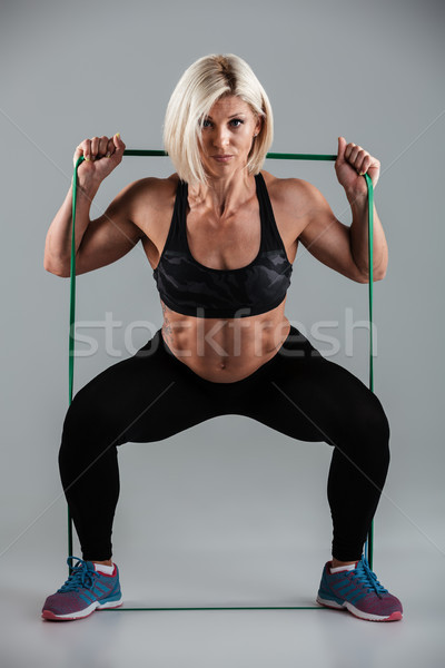 Stock photo: Portrait of strong sports woman doing sit-ups while stretching w