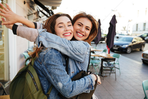 Two young happy brunette girls hugging each other, looking at ca Stock photo © deandrobot