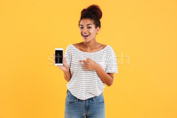 Happy african lady showing smartphone with blank screen isolated Stock photo © deandrobot