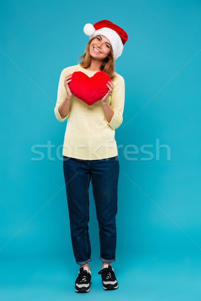 Full length photo of cheerful pretty woman in Santa's hat holding soft red heart, looking at camera Stock photo © deandrobot