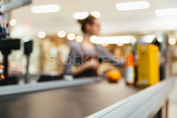 Young female cashier scanning grocery items Stock photo © deandrobot