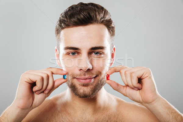 Portrait of a smiling man holding capsules at his face Stock photo © deandrobot