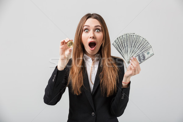 Shocked businesslady holding golden bitcoin and dollars in hands isolated Stock photo © deandrobot