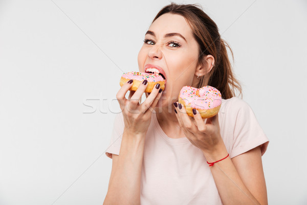 Close up portrait of a hungry greedy girl eating donuts Stock photo © deandrobot