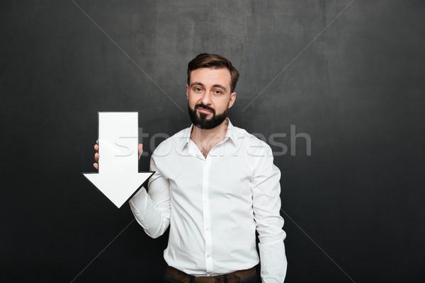 Picture of pessimistic upset man 30s holding blank speech arrow  Stock photo © deandrobot