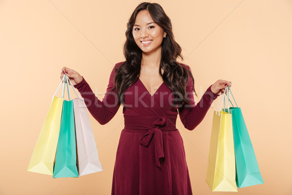 Attractive sian woman in elegant maroon dress shopping and showi Stock photo © deandrobot