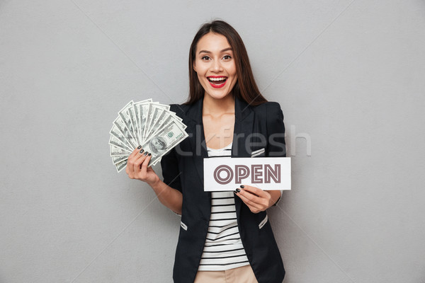 Cheerful asian business woman holding nameplate open and money Stock photo © deandrobot