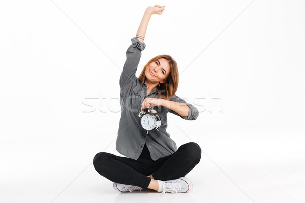 Portrait of a smiling young girl showing alarm clock Stock photo © deandrobot