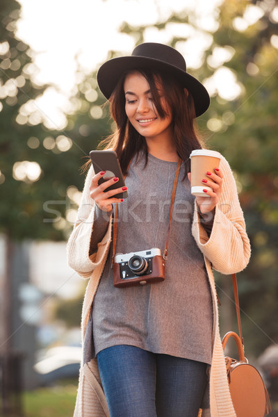 Young attractive asian woman in black hat texting sms on mobile  Stock photo © deandrobot