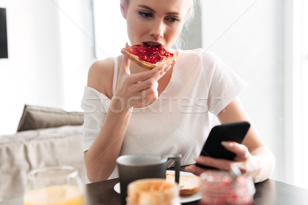 Focused blonde lady eating bread with jam amd using smartphone Stock photo © deandrobot