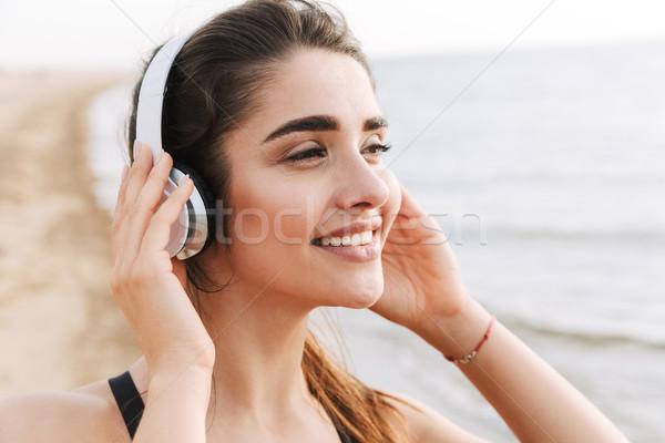 Szczęśliwy młodych sportsmenka słuchawki plaży Zdjęcia stock © deandrobot