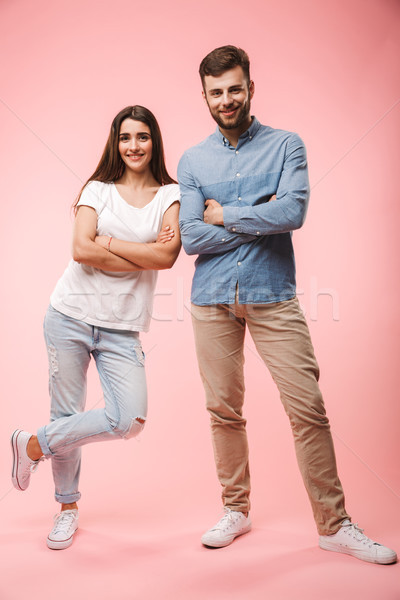 Full length portrait of a smiling young couple Stock photo © deandrobot
