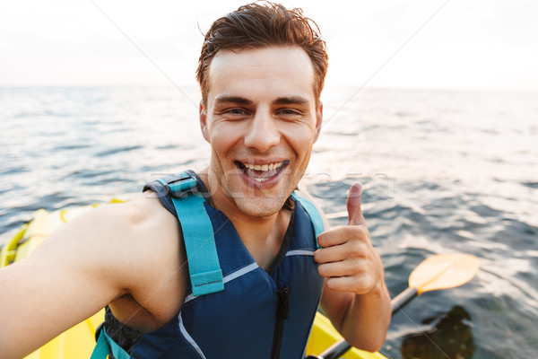 Handsome man kayaking on lake sea in boat make selfie by camera. Stock photo © deandrobot