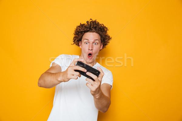 Fiatal barna hajú fickó lezser póló játszik Stock fotó © deandrobot