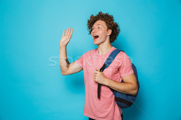 Image of student man with curly hair wearing casual clothing and Stock photo © deandrobot