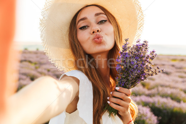 Cheerful young girl in straw hat holding lavender bouquet Stock photo © deandrobot