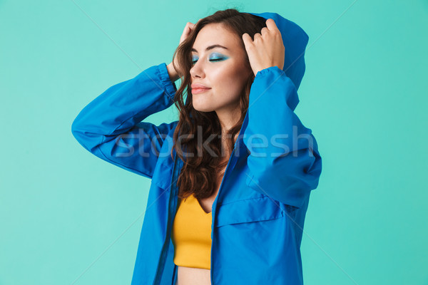 Photo of stylish young woman 20s in streetwear putting on hood o Stock photo © deandrobot