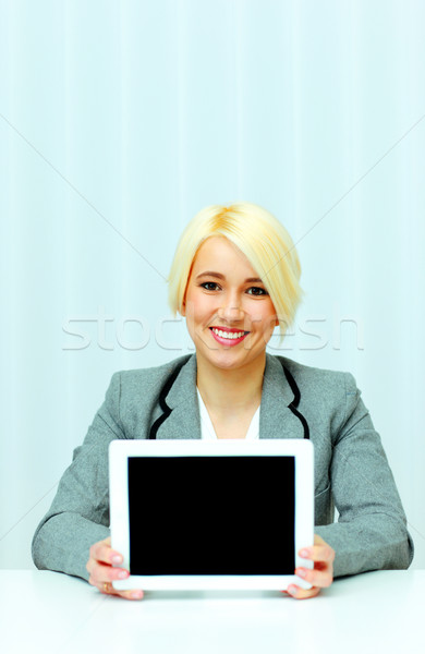 Happy beautiful businesswoman showing screen of a tablet computer in office Stock photo © deandrobot