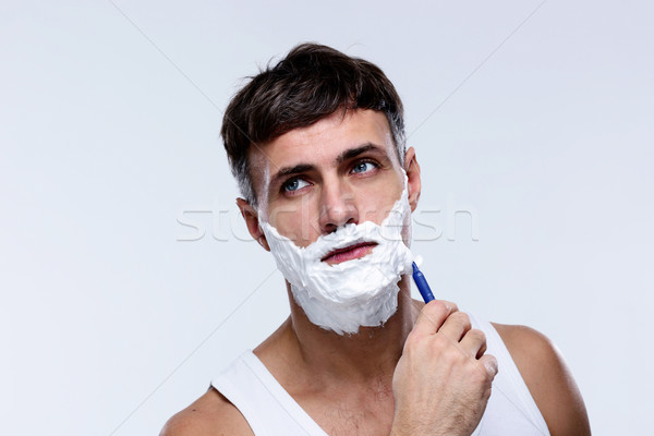 Portrait of a man shaving and looking away Stock photo © deandrobot