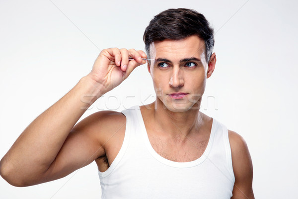 Handsome man removing eyebrow hairs with tweezing Stock photo © deandrobot