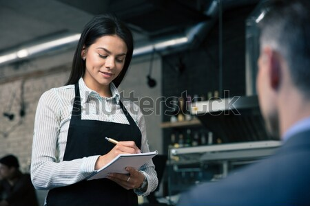 Charming female waiter in apron writing order Stock photo © deandrobot