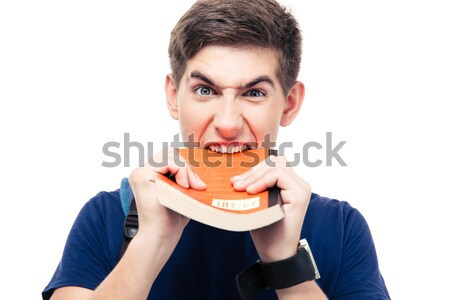 Angry male student biting book Stock photo © deandrobot
