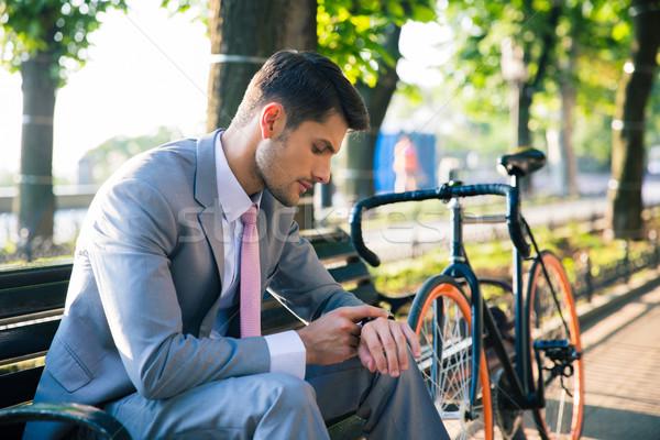 üzletember néz karóra kint fiatal ül Stock fotó © deandrobot