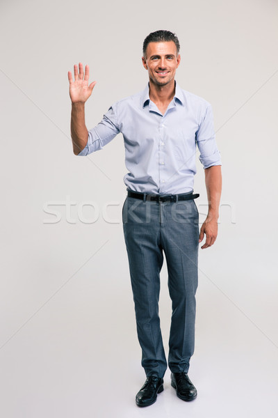 Businessman showing greeting gesture with palm Stock photo © deandrobot