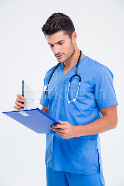 Portrait of a male doctor reading clipboard Stock photo © deandrobot