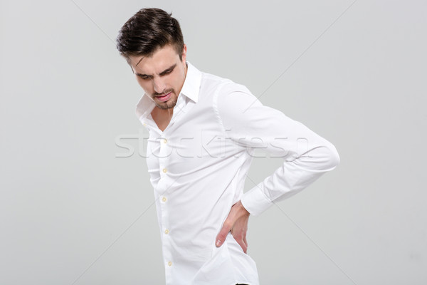 Handsome young man has a backache Stock photo © deandrobot