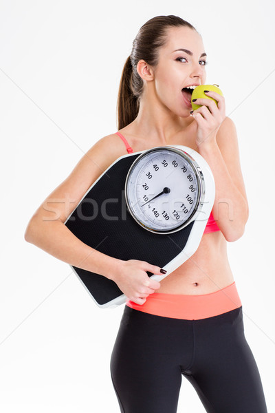 Pretty content sportswoman eating apple and holding weighing scale Stock photo © deandrobot