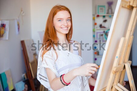 Beautiful happy woman holding blank screen tablet in art workshop Stock photo © deandrobot