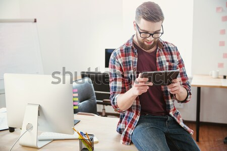 Cheerful young man sitting on the table and using smartphone Stock photo © deandrobot