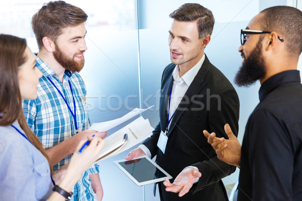 Young business people standing and talking with chief executive  Stock photo © deandrobot