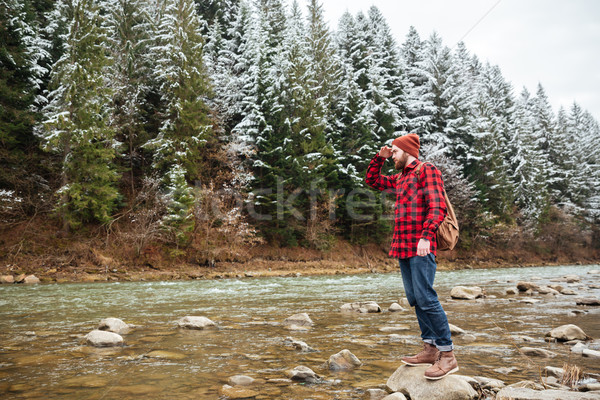 Male hiker standing on the stone in river Stock photo © deandrobot