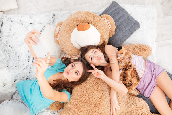 Kettő játékos nővérek küldés készít okostelefon Stock fotó © deandrobot