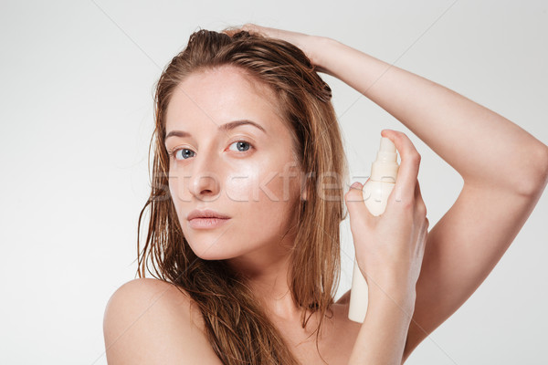 Attractive woman spraying hairspray Stock photo © deandrobot