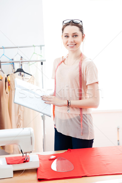 Happy woman seamstress standing and working with red fabric  Stock photo © deandrobot