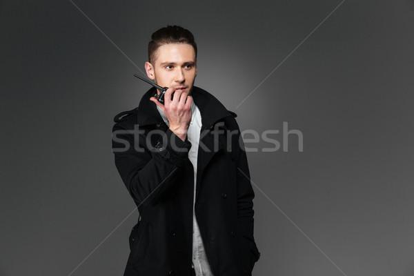 Сток-фото: серьезный · молодым · человеком · черный · пальто · говорить