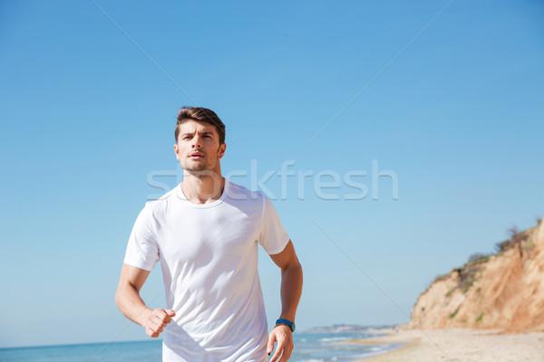 Młodych sportowiec jogging plaży biały tshirt Zdjęcia stock © deandrobot