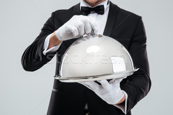 Serving tray with cloche holded by butlers hands in gloves Stock photo © deandrobot