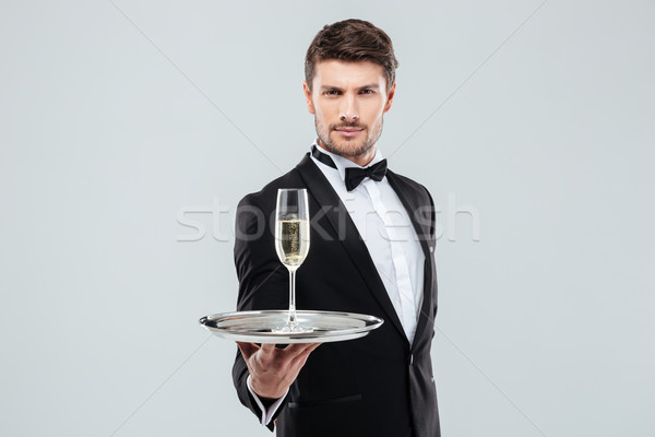 Attractive young butler in tuxedo offers you glass of champagne Stock photo © deandrobot