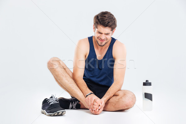 Fitness man sitting and suffering with foot pain Stock photo © deandrobot