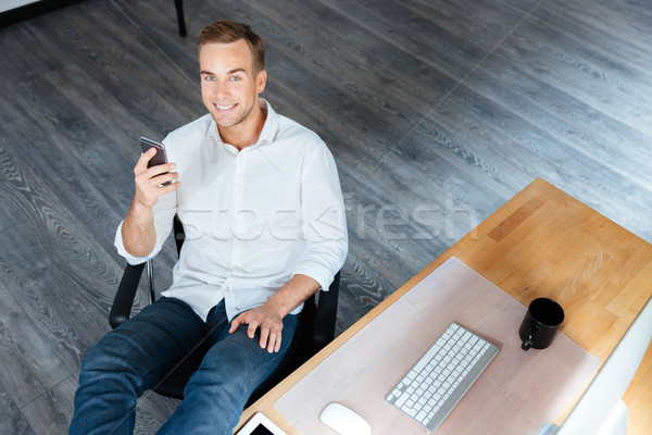 Cheerful young businessman sitting and using mobile phone at workplace Stock photo © deandrobot