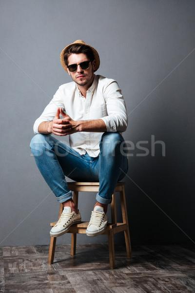 Attrattivo giovane occhiali da sole Hat seduta Foto d'archivio © deandrobot
