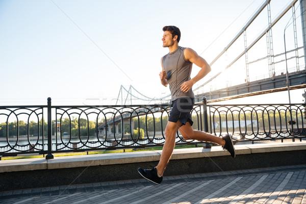 Side view of sportsman running along bridge at sunset light Stock photo © deandrobot