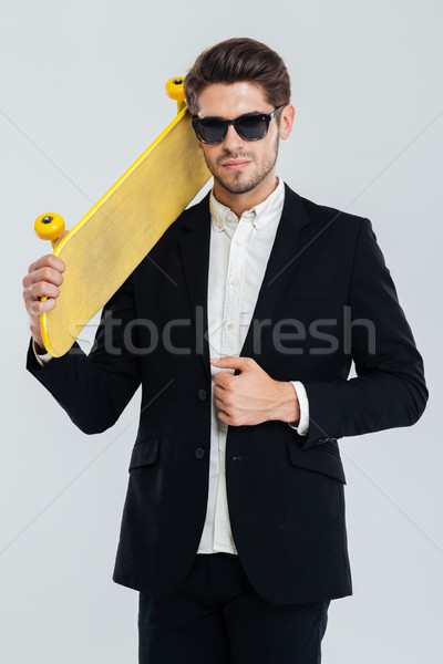 Serious businessman in sunglasses holding yellow skateboard on his shoulder Stock photo © deandrobot