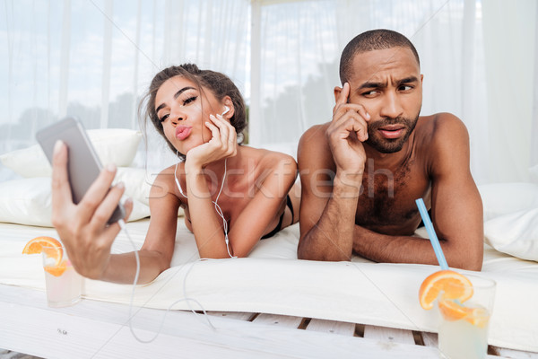 Girl making selfie with displeased boyfriend Stock photo © deandrobot