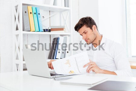 Side view of a bearded casual businessman sitting with laptop Stock photo © deandrobot
