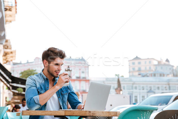 Smiling cheerful casual man using laptop outdoors and drinking coffee Stock photo © deandrobot